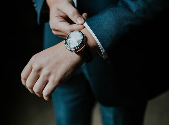 A man adjusting the cuff of his business suit and showing off a luxury watch whilst doing so.
