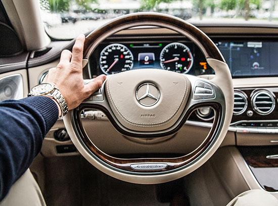 A close up of the cream coloured interior of the drivers side of a mercedes benz with the a male driver holding onto the steering wheel with the mercedes insignia with his left hand.