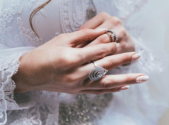 A closeup shot of a lady in a wedding dress putting a diamond ring on her finger.