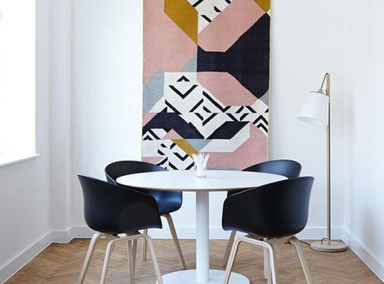 A room with a round table and chairs and abstract artwork on the wall.
